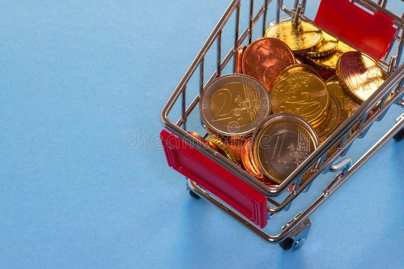 En shoppingvagn med euromynt royaltyfria foton