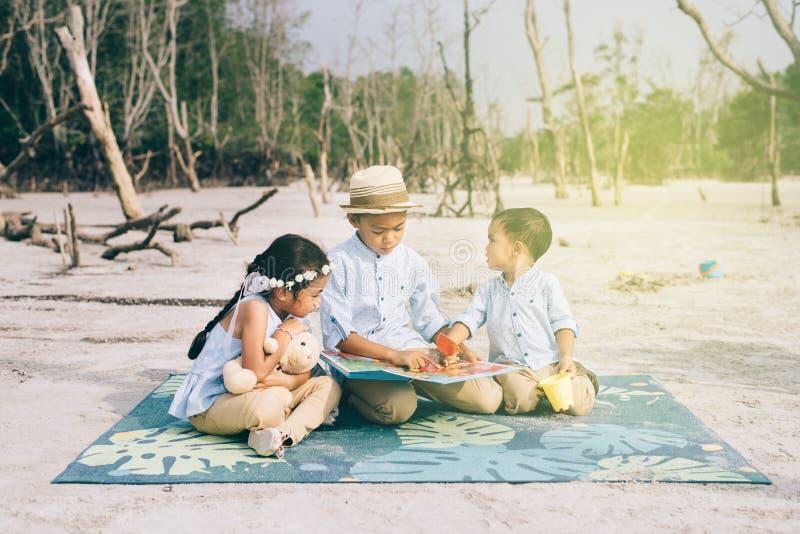 En Siblings die samen in openlucht toevallig dragen lezen lachen stock afbeeldingen