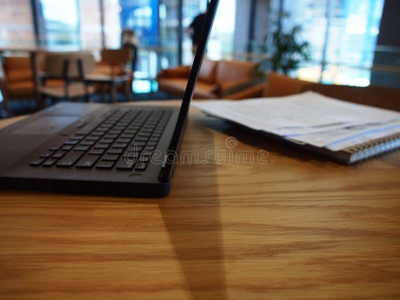 En sidosikt av en öppen bärbar dator på en tabell arkivbilder