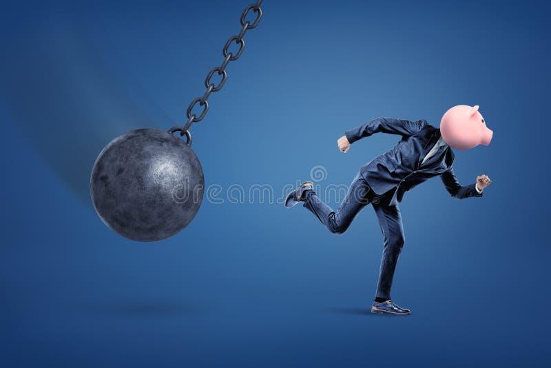 En sidosikt av en färdig affärsman med en encentmyntbank i stället för hans huvud som kör från en rivningboll royaltyfri foto