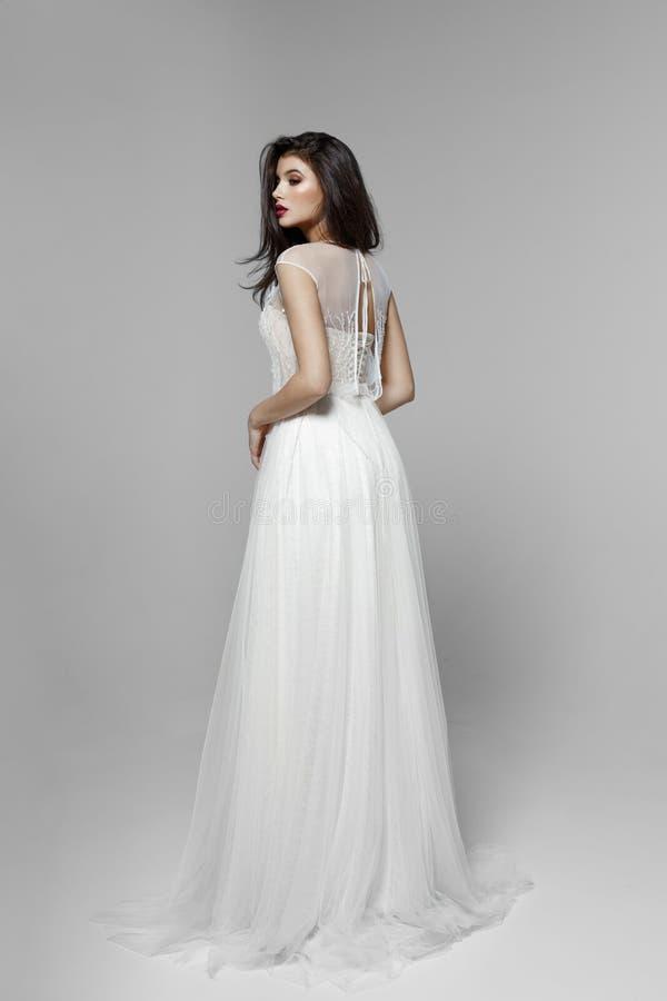 En sidosikt av en försiktig brunettmodell i klassisk vit bröllopsklänning, på vit bakgrund royaltyfria bilder