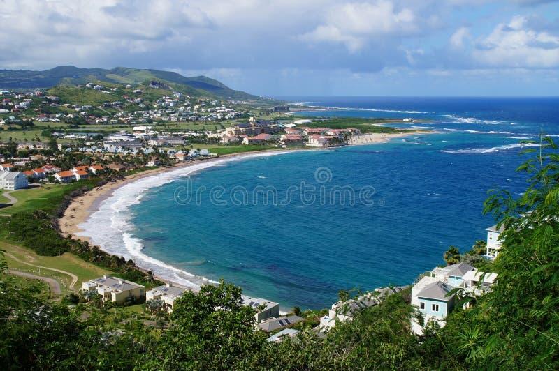 En sikt över ön för St Kitts med bostadsområde och beaces på förgrunden och frodiga gröna kullar på bakgrunden royaltyfri foto