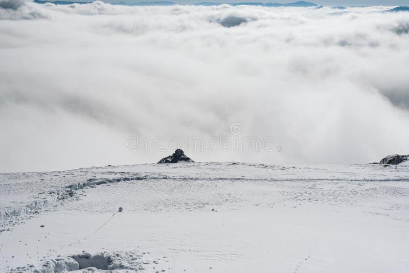En sikt av dalen från kanten av en snöig lutning royaltyfri bild