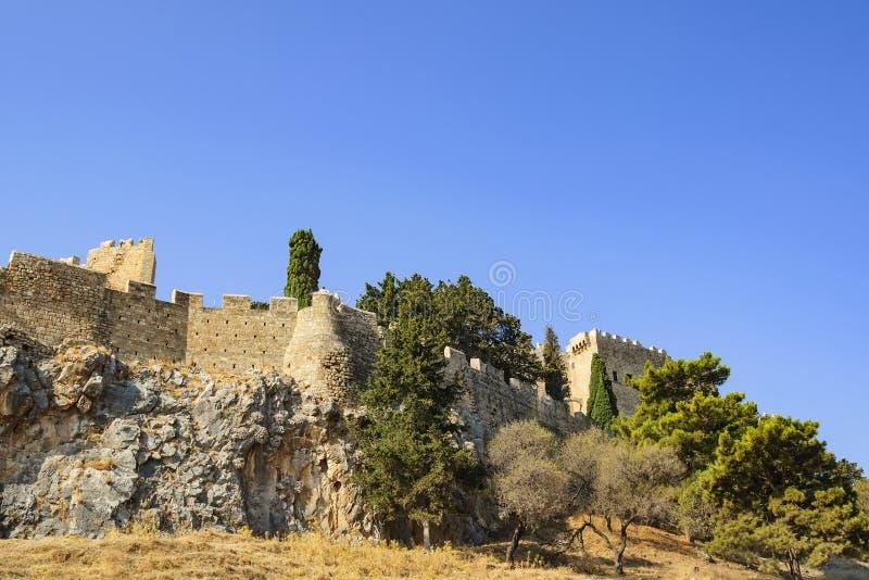 En sikt av de forntida väggarna och tornen av akropolen av Lindos Rhodes ö, Grekland arkivfoton