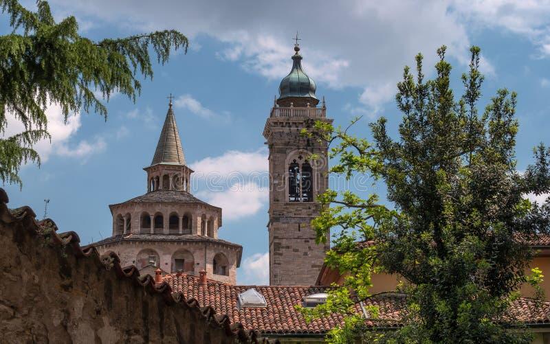 En sikt av den kyrkliga kupolen för ` s och ett klockatorn till och med filialerna av ett träd bergamo italy I förgrunden finns d arkivfoto