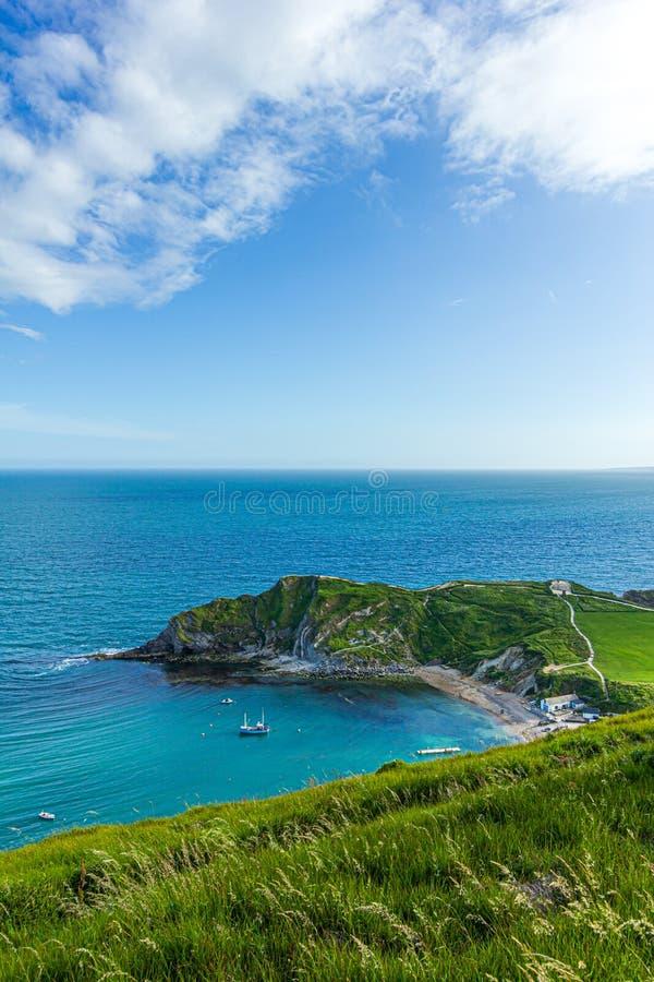En sikt av den Lulworth lilla viken längs den Jurrassic kusten i Dorset under en majestätisk blå himmel och några vita moln royaltyfri fotografi