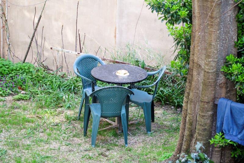 En sikt av den medelhavs- trädgården med möblemang av en uppsättning av tre gröna stolar för plast- och en tabell Ferier och tyck royaltyfri foto