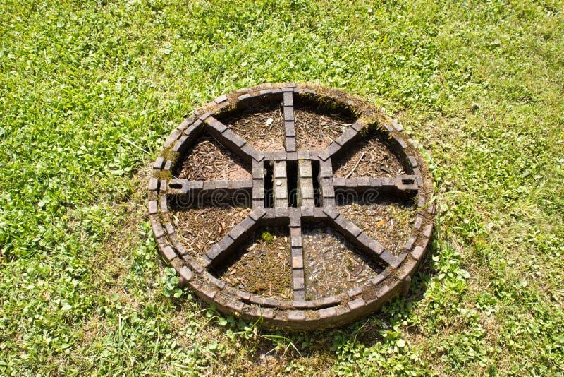 En sikt av den metallkanalluckan och gräsmattan royaltyfri fotografi