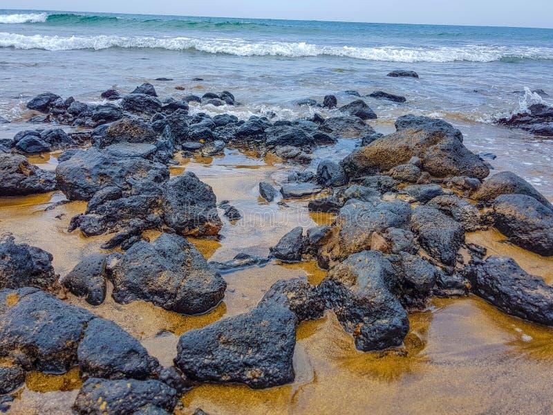 en sikt av den sandiga och steniga kustlinjen på en strand i Lanzarote, kanariefågelöar, Spanien royaltyfri foto