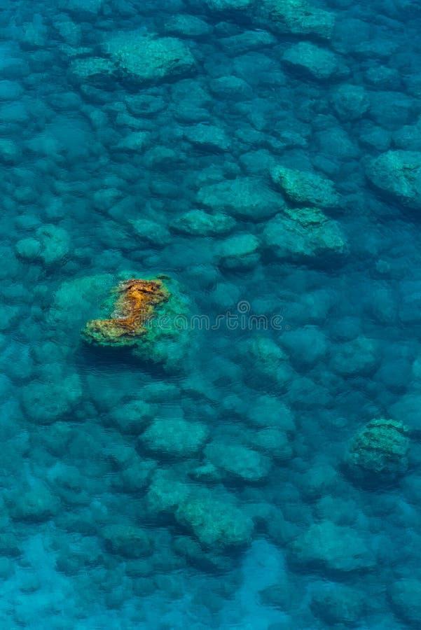 En sikt av det kristallklara havet som är många vaggar under vatten, och vagga att sticka ut ut ur vattnet arkivbilder