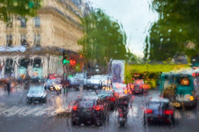 En sikt av gatan och bilarna till och med vått exponeringsglas royaltyfri foto
