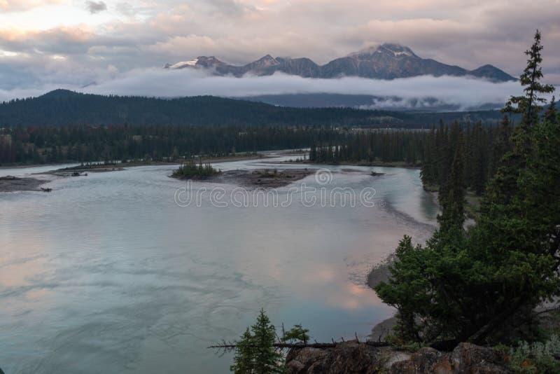 En sikt av jaspisen och den Athabasca floden, som den väver dess väg till och med Jasper National Park, Kanada P? en molnig dag royaltyfria foton