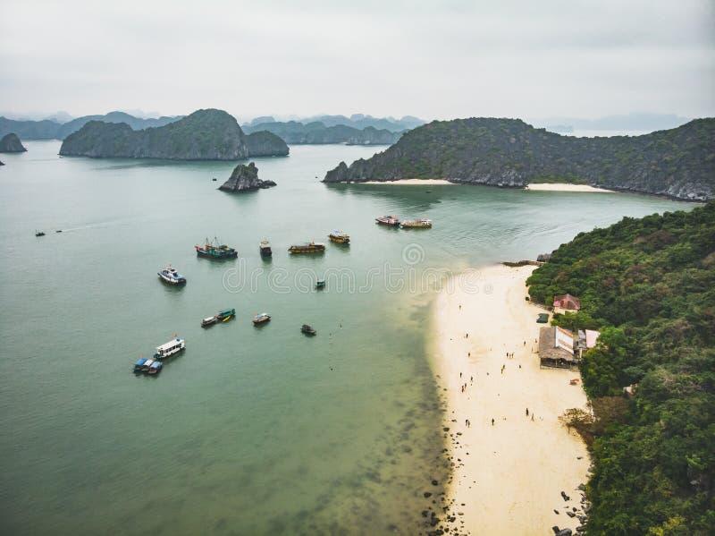 En sikt av en sandig strand och en Halong fjärd med några fartyg som skjutas från överkant av apaön royaltyfri foto
