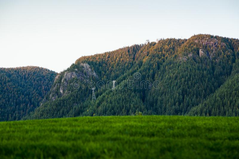 En sikt av skogshönsberget, norr Vancouver som tänds av inställningssolen royaltyfri fotografi