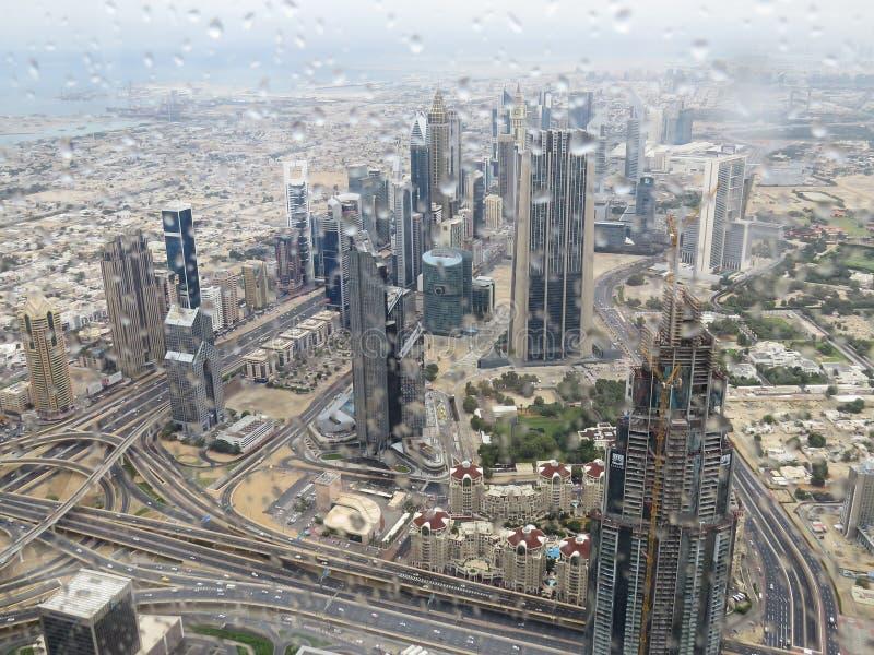 En sikt av staden av Dubai från observationsdäcket av det Burj Khalifa tornet till och med exponeringsglas med regndroppar arkivbild