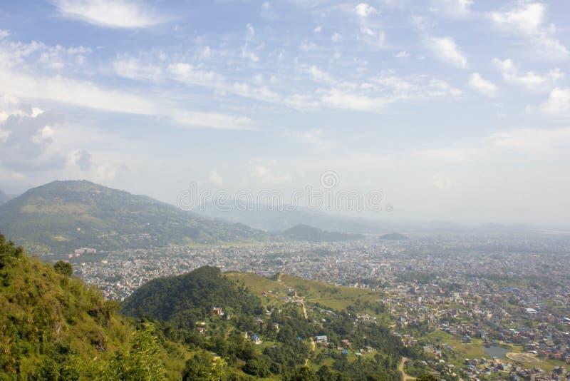 En sikt av staden i en grön bergdal i misten under den blåa himlen och de vita molnen fotografering för bildbyråer