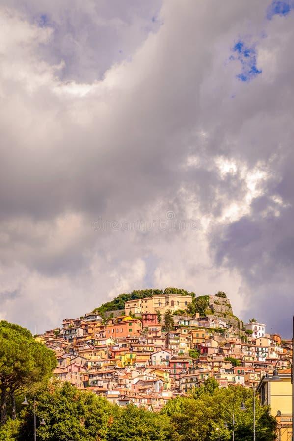 En sikt av staden Rocca di Far i Lazio, Italien med det mörka molnet arkivfoton