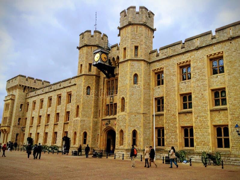 En sikt av tornet av London med turister som besöker museet med moln i backgroen arkivfoto