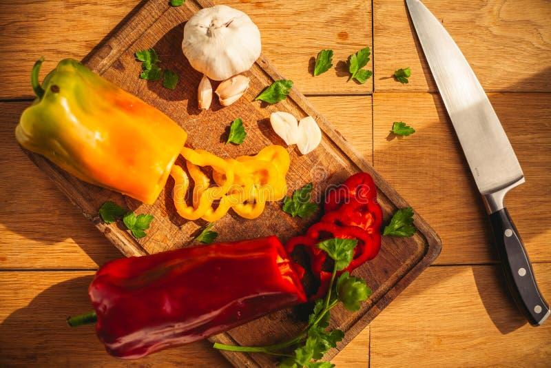 En sikt av två peppar på skärbrädan med några ingredienser runt om dem: vitlök persilja, olja arkivfoto