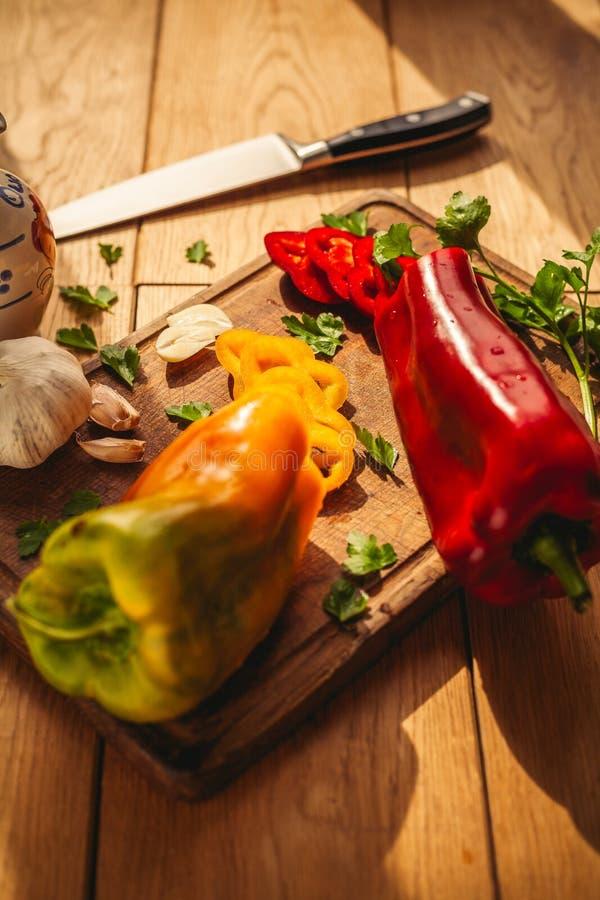 En sikt av tv? peppar p? sk?rbr?dan med n?gra ingredienser runt om dem: vitl?k persilja, olja arkivfoton