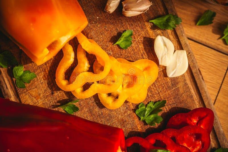 En sikt av tv? peppar p? sk?rbr?dan med n?gra ingredienser runt om dem: vitl?k persilja, olja royaltyfria foton