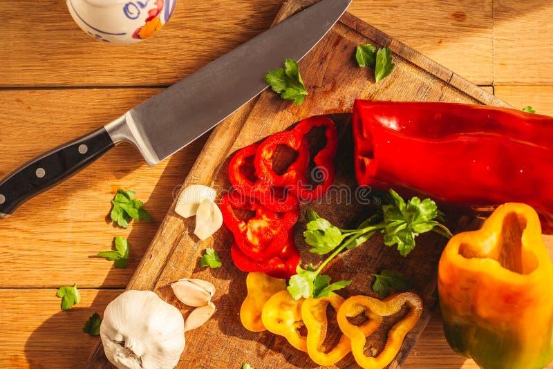 En sikt av tv? peppar p? sk?rbr?dan med n?gra ingredienser runt om dem: vitl?k persilja, olja royaltyfri bild