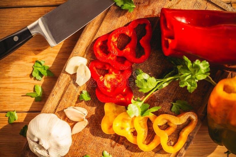 En sikt av tv? peppar p? sk?rbr?dan med n?gra ingredienser runt om dem: vitl?k persilja, olja arkivbild
