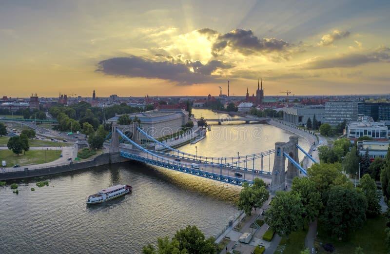 En sikt för öga för fågel` s av broar, ett skepp på floden och inställningssolen royaltyfri fotografi
