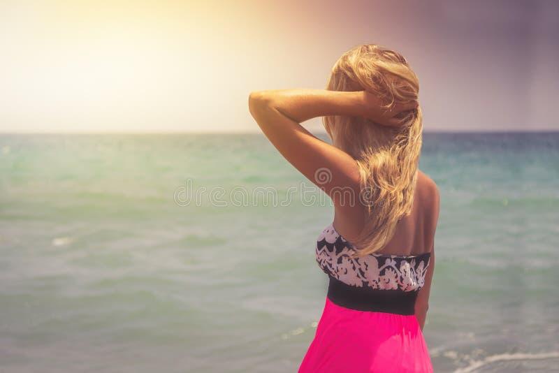 En sikt för tillbaka sida på en underbar ung kvinna som håller ögonen på till havet och lyfter hennes händer på soluppgång arkivbild