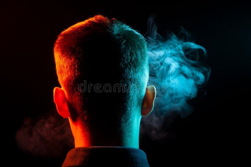 En sikt från baksidan på huvudet av en man i en skjorta som röker ett v arkivfoto