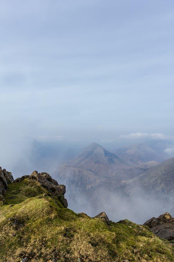 En sikt från en bergtoppmöte med flera andra toppmöten och vita moln för höjd royaltyfri fotografi
