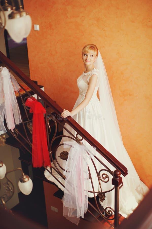 En sikt på ett nätt blont brudanseende på trappan royaltyfria bilder