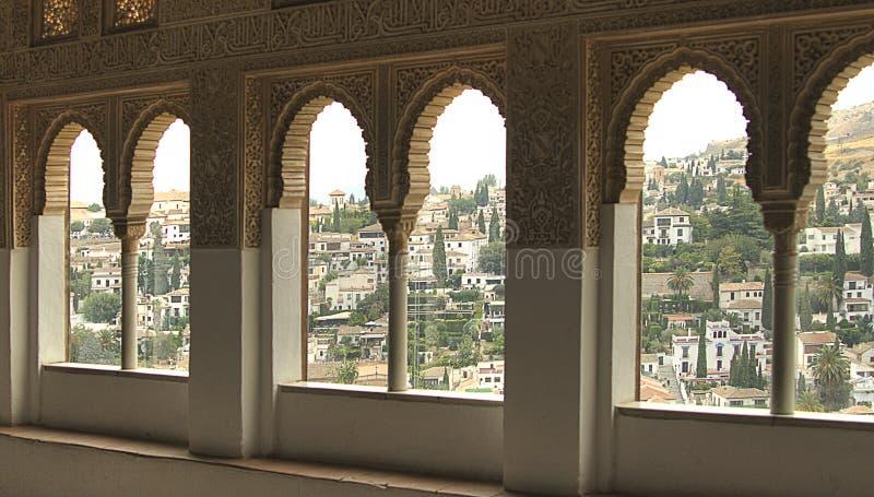 En sikt till Granada till och med ett fönster i slotten av Alhambra royaltyfri foto