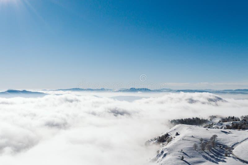 En sikt uppifrån av ett snöig berg till en dal som täckas av en dimma på en solig dag med en klar blå himmel arkivbilder