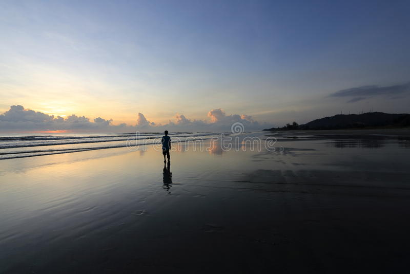 En silhouetted man på en strand royaltyfri foto