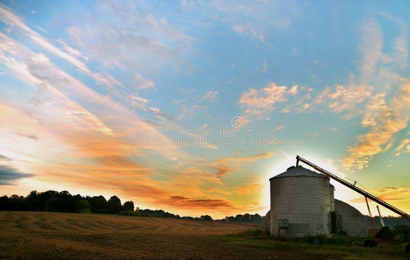 En silo på en lantgård på soluppgång arkivbild