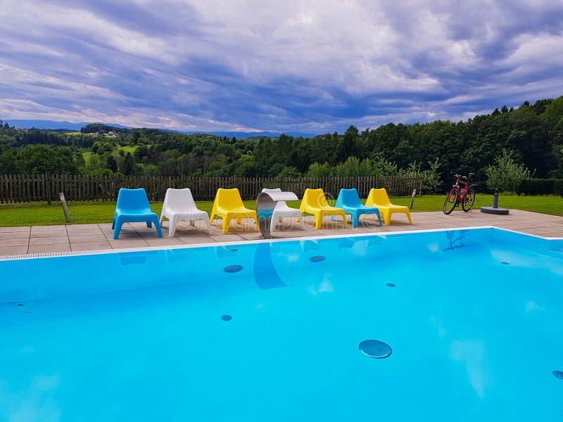 en simbassäng med stolar på sidan royaltyfri fotografi