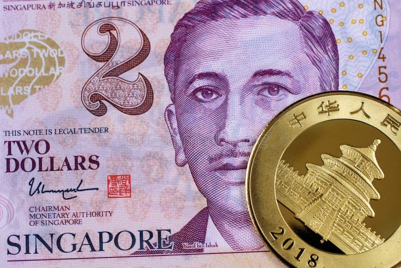 En Singapore två dollar anmärkning med ett kinesiskt guld- mynt arkivfoton