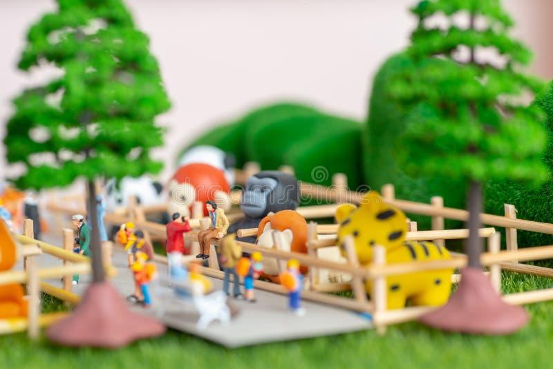 En själv konstruerade miniatyrleksakerbegrepp av folk på zoo royaltyfri foto