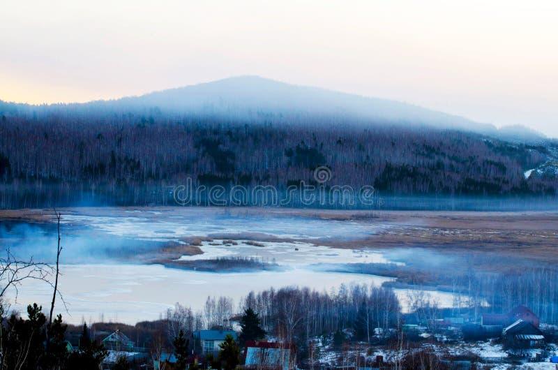 En sjö med ett berg i bakgrunden arkivfoto
