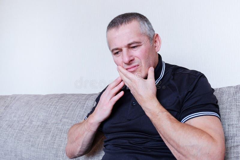 En sjuk man med en tandvärk Lidande är en sinnesrörelse av kval på hennes framsida Begreppet av vård- royaltyfria foton