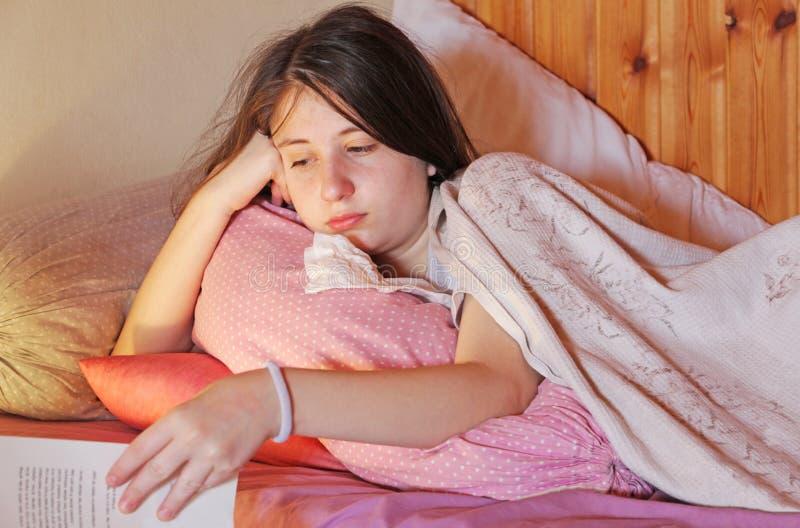 En sjuk tonårs- flicka ligger i säng arkivbild