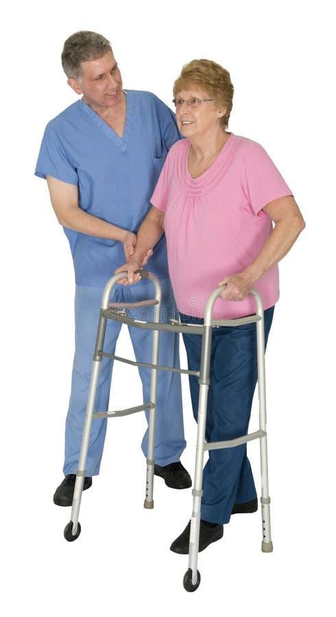 Sjuksköterskan sjukgymnastik, mognar den höga gammalare kvinnan arkivbild