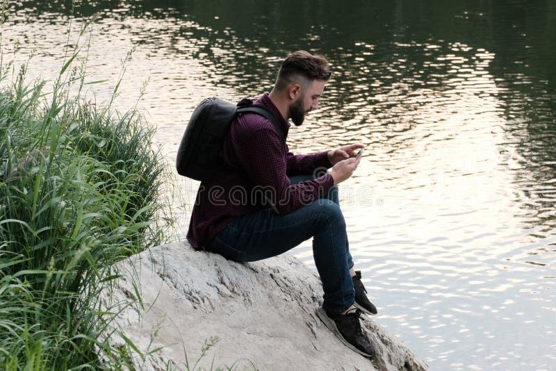 En skäggig grabb i jeans och en T-tröja med en telefon i hans händer sitter på en sten vid floden Handelsresande med en ryggsäck  royaltyfri foto