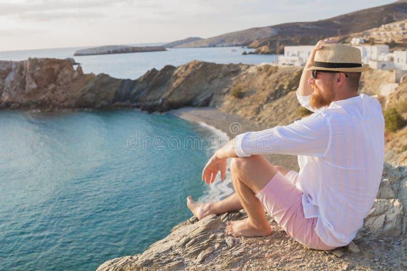 En skäggig hipsterman på semester sitter på en brant kust och ser in i avståndet royaltyfri foto