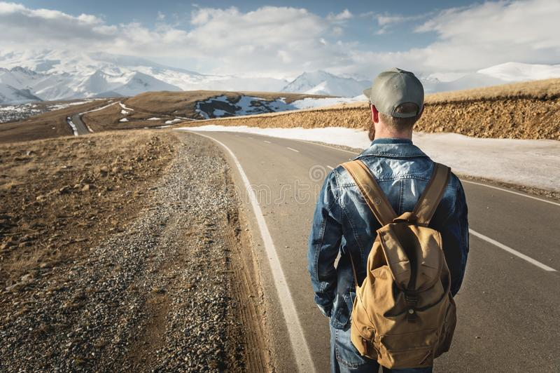 En skäggig man i ett lock med en ryggsäck som är klar att gå en lång väg En man på en landsväg mot bakgrunden av berg arkivfoton