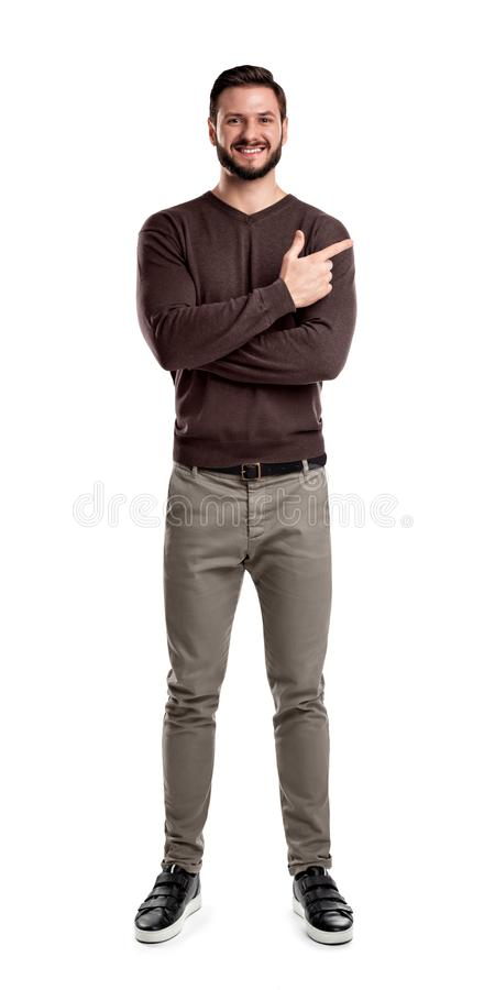 En skäggig man i tillfällig kläder ler med hans armar vikta men som fortfarande från sidan indikerar med hans pekfinger royaltyfri bild