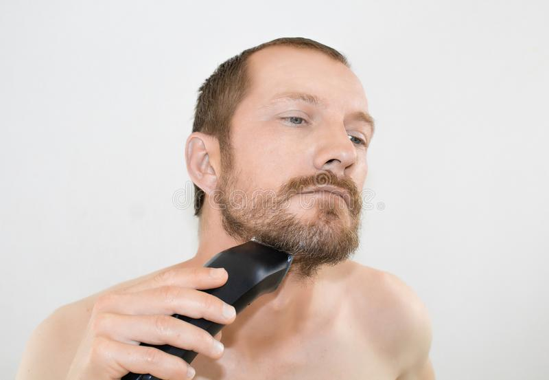 En skäggig man rakar en elektrisk boite royaltyfria bilder