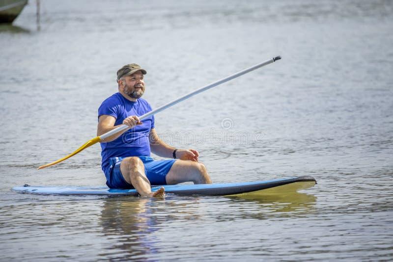 En skäggig man som paddlar i havet arkivbild