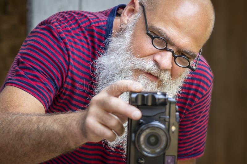 En skäggig man som tar ett fotografi royaltyfri fotografi